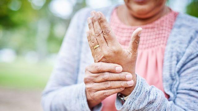Imagem de senhora apertando uma mão com a outra, indicando local com artrite