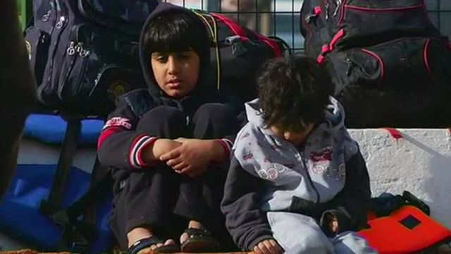 Migrant children waiting with luggage