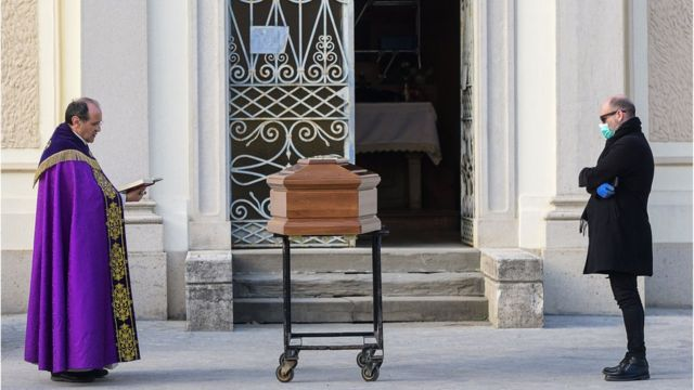 Diante de um caixão, um padre abençoa rapidamente um morto em frente a uma igreja na Itália