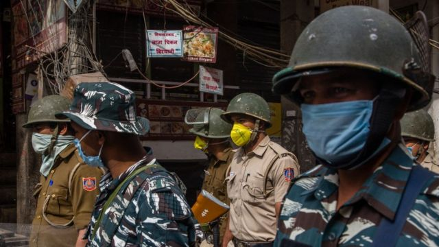 Image shows Indian policemen wearing protective masks
