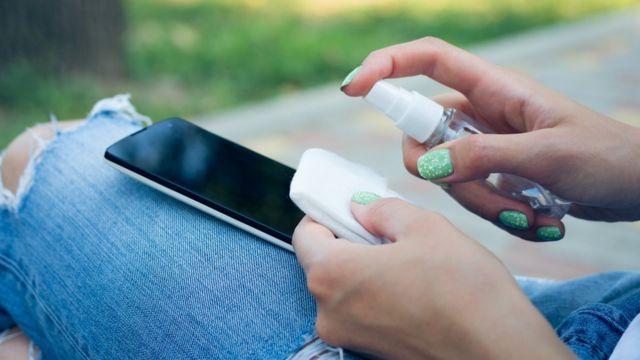 Mujer limpiando su celular