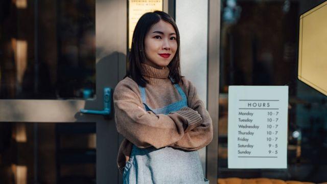 Imagen de una mujer frente a la puerta de una oficina.
