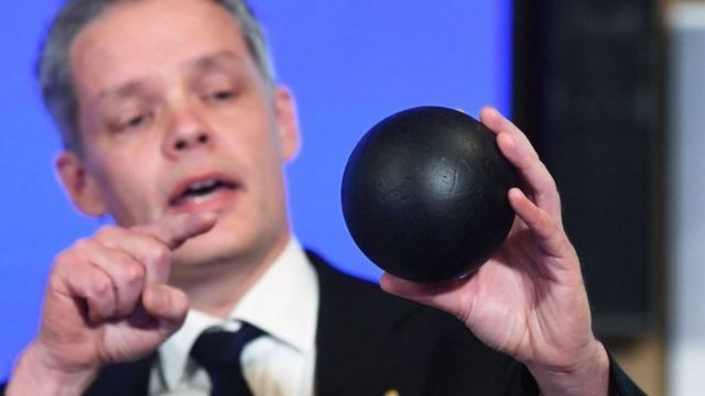 Nobel komitesinden Ulf Danielsson, ödülün açıklandığı basın toplantısında kara bir top kullanarak kara delikleri izah ediyor