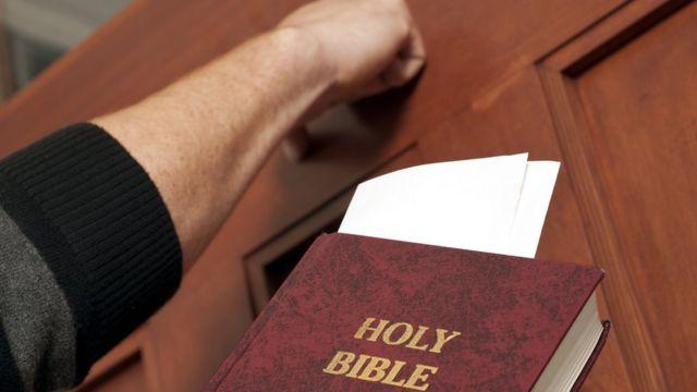 Foto de banco de imagens com pessoa batendo na porta com bíblia na mão