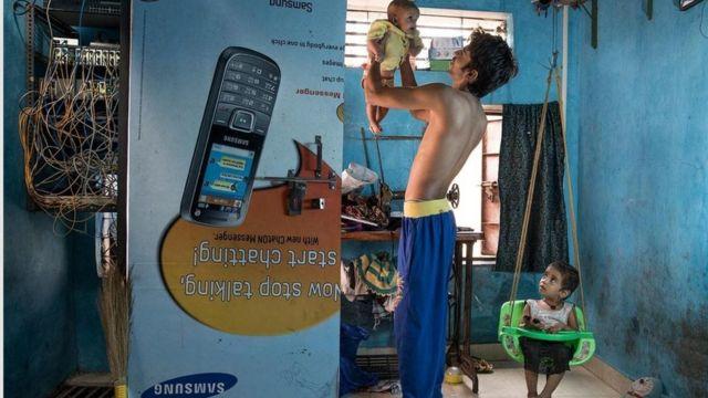 رضوان شيخ وابنتيه في منزلهم في زقاق في مومباي ، ويأمل أن تصبح ابنته جافينه البالغة من العمر ثلاث سنوات طبيبة.