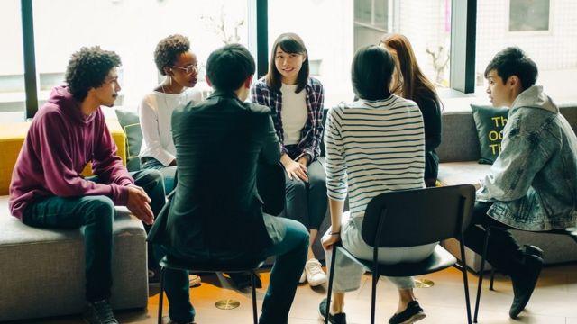 Un groupe de jeunes assis en cercle sur des chaises, tenant une discussion amicale.