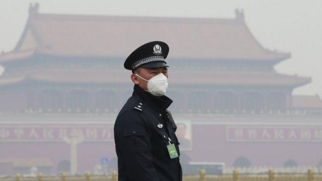 Agente de segurança usa máscara em Pequim