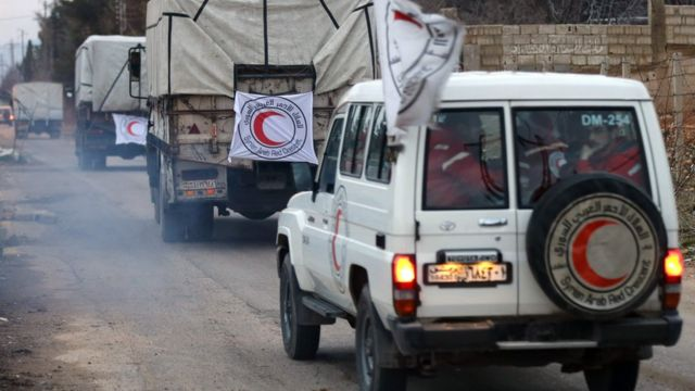 Vehicles from the Syrian Arab Red Crescent drive in a convoy on the outskirts of the besieged rebel-held Syrian town of Madaya, on January 11, 2016.