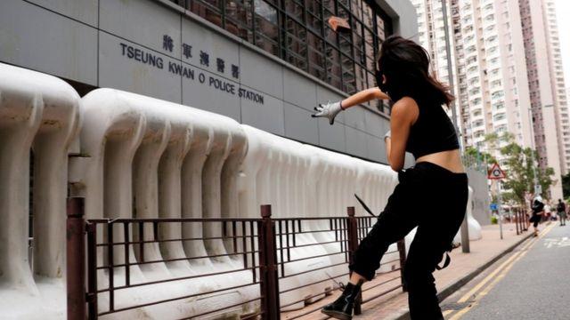 Una mujer lanzando piedras en una estación de policía en Hong Kong.