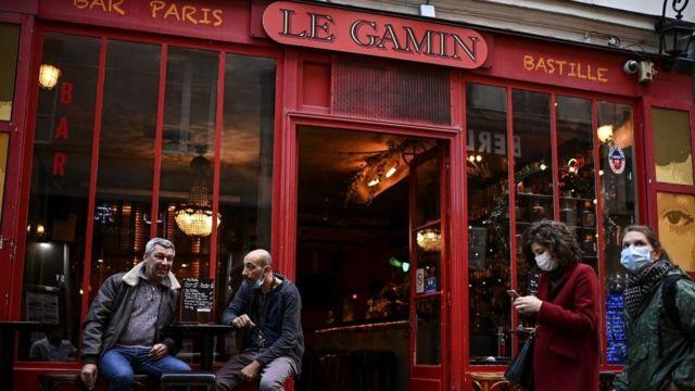 Paris'te bir barın önünde oturanlar.