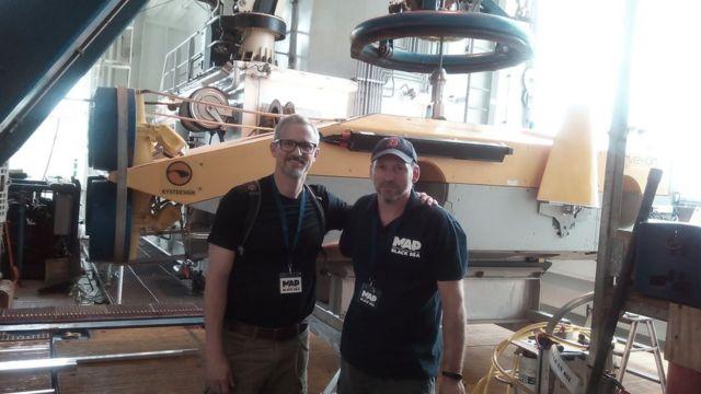 Запорожский археолог Дмитрий Кобалия (справа) и его коллега из Украины Тарас Певный (слева) на фоне робота, который сканирует морское дно