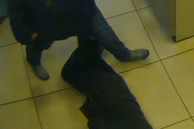 Bank CCTV shows pensioner lying next to cash machines (Essen police photo)