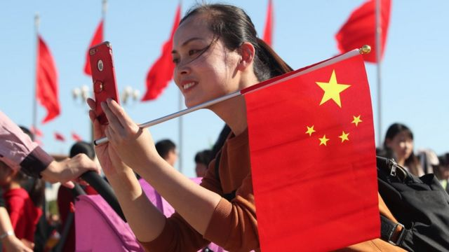 A tourist holding a Chinese national flag takes pictures at the Tiananmen Square during the Chinese National Day holiday on October 3, 2018 in Beijing, China.