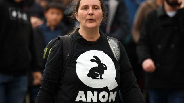 Mulher com camisa com o logo da QAnon