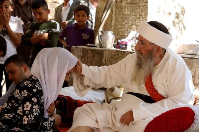 """"""" الشيخ الإيزيدي الكبير"""" يبارك امرأة في """"عيد ئيزي"""" بعد ثلاثة أيام من الصيام. أكتوبر/تشرين الأول 2017 في معبد لالش بإقليم كردستان العراق"""