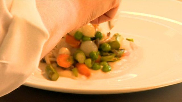 Chef dishing vegetables on to plate
