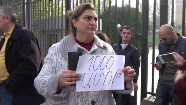 """Qadının əlində """"1000 dram (vermək) ayıbdır"""" şüarını tutur."""