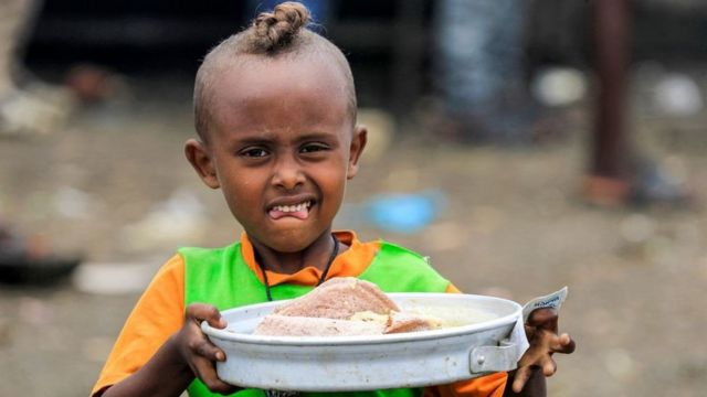 A child walks with a tray carrying soup and traditional Injera Ethiopian sour flatbread as Ethiopian refugees of the Qemant ethnic group queue for food at a camp in the village of Basinga in Basunda district of Sudan's eastern Gedaref region on August 10, 2021.