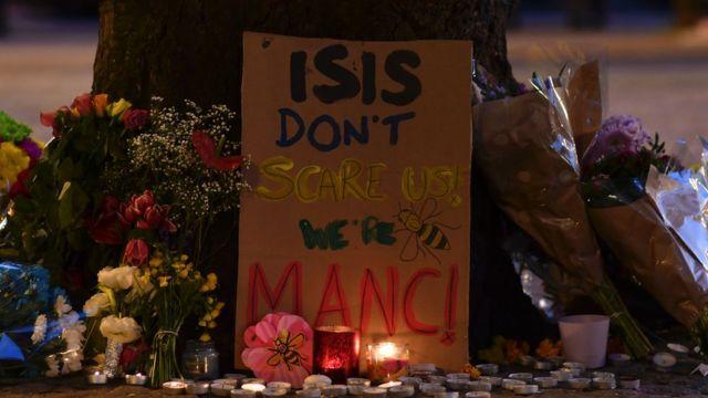 """Manchester'da hayatını kaybedenlerin anmasına """"IŞİD bizi korkutmuyor, biz Manchesterlıyız"""" yazılı karton bırakıldı."""