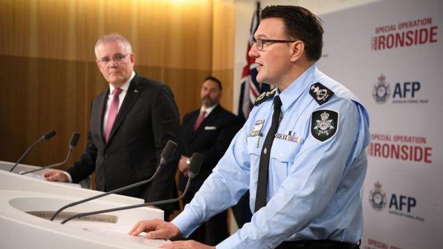 اسکات موریسون نخست وزیر استرالیا (سمت چپ) در کنفرانس خبری بزرگترین عملیات پلیس کشور حضور داشت و آن را تاریخی خواند