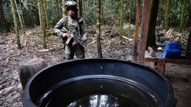コカイン工場に火を放つ前に現場を調べる警官