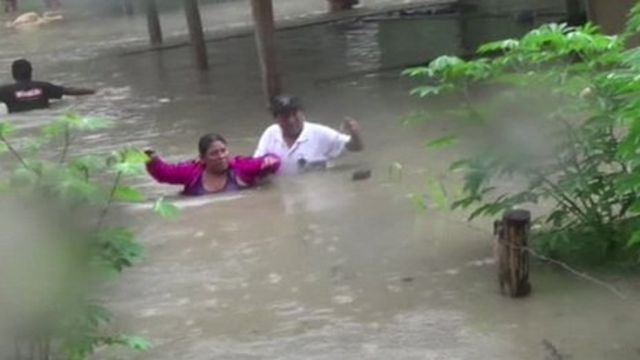 People struggling through water that is up to their chests