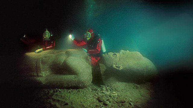 Divers and Egyptian statue