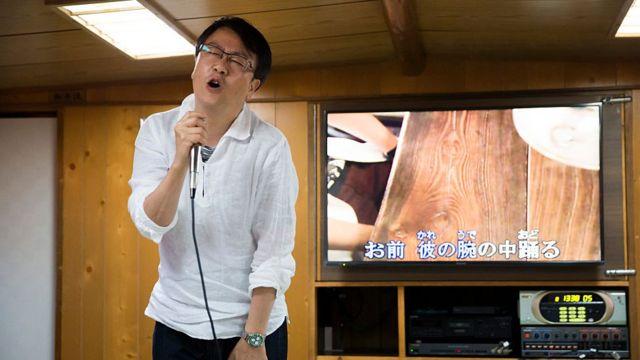 A customer sings a song using a karaoke machine