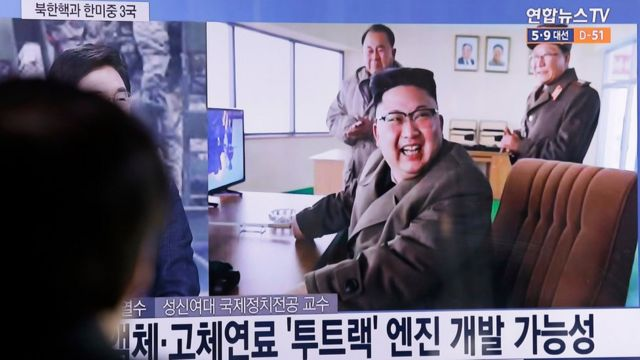 """A man watches a TV news program showing an image, published in North Korea""""s Rodong Sinmun newspaper, of North Korean leader Kim Jong Un at the country""""s Sohae launch site, at Seoul Railway station in Seoul, South Korea, Sunday, March 19, 2017"""