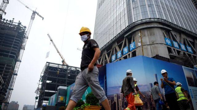Китайский рабочий на фоне строящегося здания