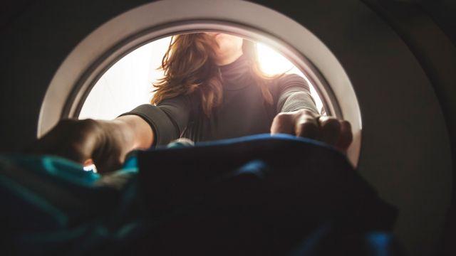 Foto de uma mulher com as mãos dentro de uma máquina de lavar, segurando um tecido que aparenta ser uma roupa