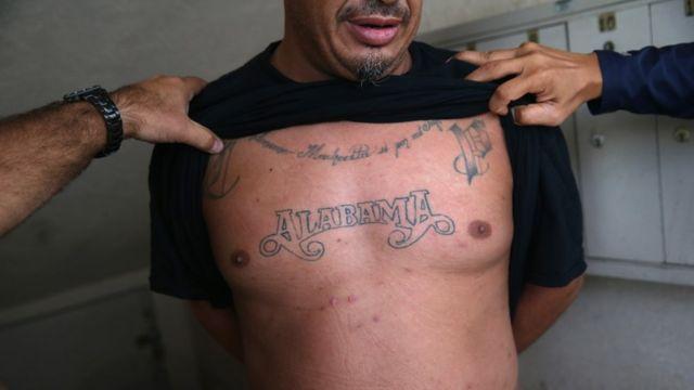 Agentes del ICE inspeccionan los tatuajes de un hombre detenido en Los Ángeles, California