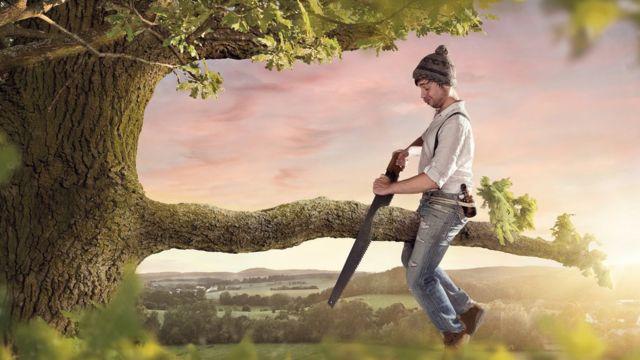 Homem cortando o galho de uma árvore na qual está sentado