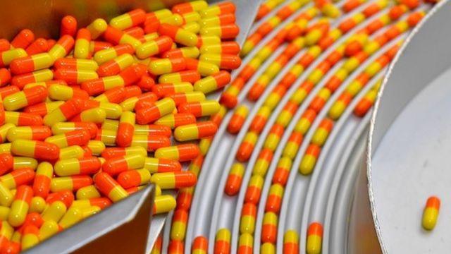 Cápsulas amarelas e laranjas organizadas dentro de uma máquina