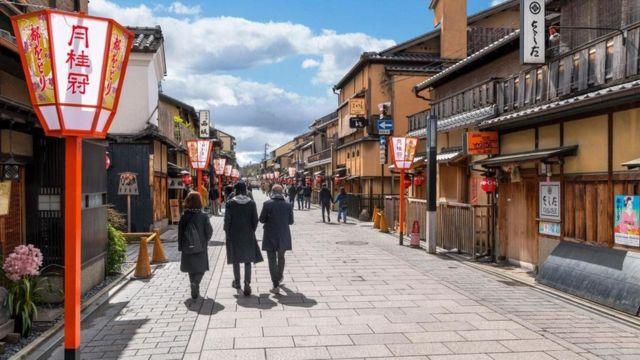Pessoas caminham pela rua em cidade japonesa