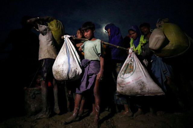 لاجئون من أقلية الروهينغيا المسلمة يحملون أمتعتهم