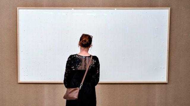 Uma mulher vê uma instalação de arte intitulada 'Pegue o dinheiro e fuja', do artista dinamarquês Jens Haaning