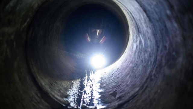 A protester uses a torch light while crawling within a sewer tunnel to see how wide it is