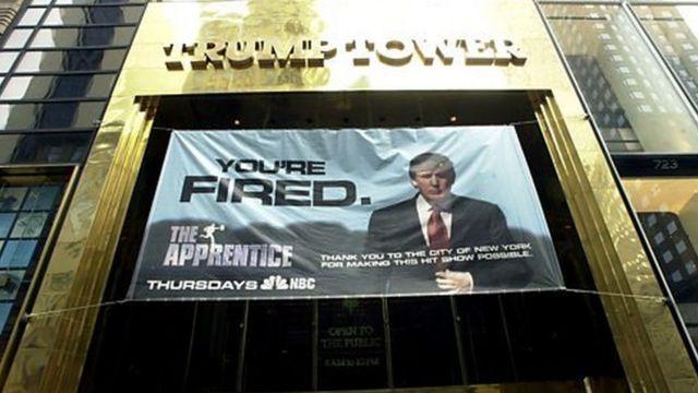 پرچمی با نشان برنامه تلویزیونی 'کارآموز' بیرون برج ترامپ، پیش از پخش اولین قسمت برنامه