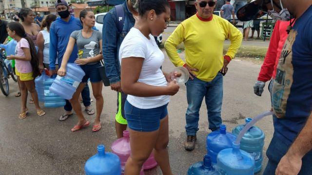 Pessoas em fila da água em Macapá