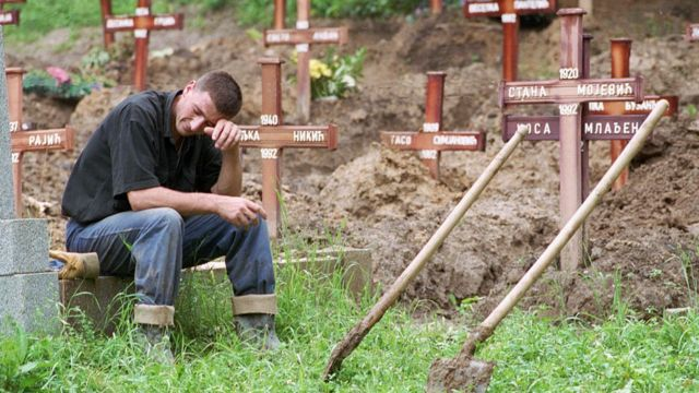 Man cries as he buries victims of the Bosnian war.
