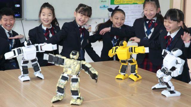 Çinli ilkokul öğrencileri ve minyatür robotlar.