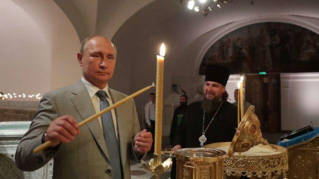 Vladimir Putin, el presidente de Rusia, encendiendo unas velas en un templo ortodoxo.