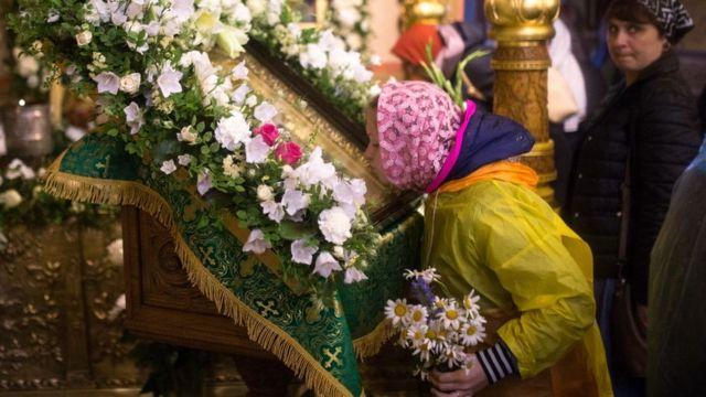 Mujer besando una figura en una iglesia ortodoxa.