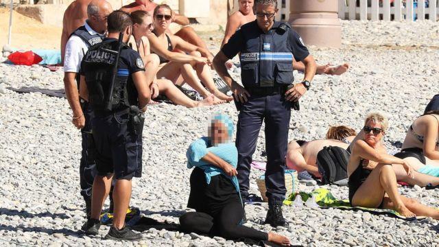 Los policías en Niza conversan con la mujer vestida en la playa.