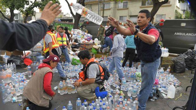 Voluntarios distribuyen agua y productos de primera necesidad.