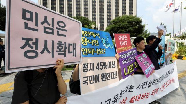한 시민단체 회원들이 정부서울청사 앞에서 '민심은 정시 확대'라는 피켓을 들고 서 있다