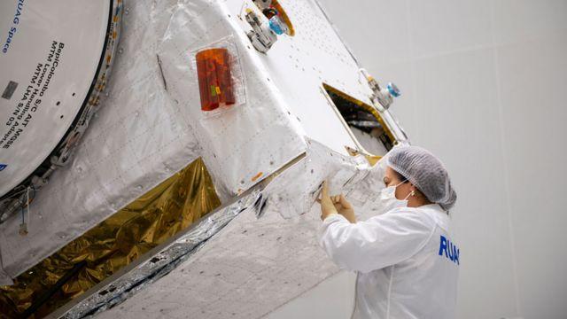 Mujere cosiendo a mano una de las mantas de aislamiento en los satélites