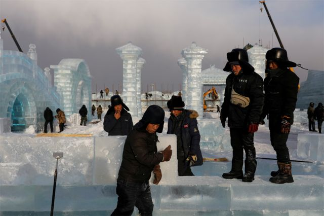Workers smoke while constructing ice structures at the site of the Harbin International Ice and Snow Festival