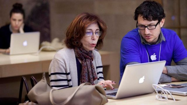 موظف وموظفة ينظران إلى شاشة كمبيوتر محمول